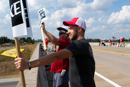 GM workers, Jeremy Hobbs (left) and Gerg Hill, strike near the south gate of the Spring Hill GM plant Friday, Sept. 27, 2019, in Spring Hill, Tenn.