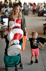 Hudson NeeSmith, 2, gave up his stroller seat so his mom, Amy, could roll the new Santa they purchased at the Nashville Flea Market, which opened in its new space Friday, Sept. 27, 2019.