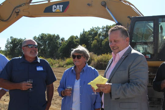 The Stoneworks Partners CEO Eric Horvath (right) smiles as he reads his speech during a toast celebrating the construction of additional homes and a five-acre harbor in Buckeye Lake on Thursday, Sept. 26, 2019 as Buckeye Lake Mayor Peggy Wells, Buckeye Lake Region Corporation Director Mike Fornataro, and others look on.