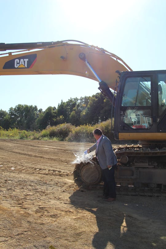 Eric Horvath, The Stoneworks Partners CEO, breaks a champagne bottle over construction equipment during a celebration of construction at The Landings at Maple Bay in Buckeye Lake on Thursday, Sept. 26, 2019.