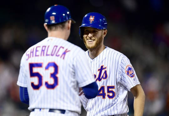 Starting pitcher Zack Wheeler #45 and first base coach Glenn Sherlock #53 of the New York Mets celebrate a single by Wheeler in the seventh inning of their game against the Miami Marlins at Citi Field on September 26, 2019 in New York.