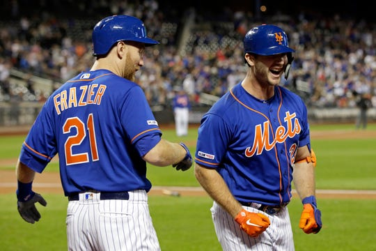 New York Mets' Pete Alonso is congratulated after hitting his 52nd home run of the season by Todd Frazier (21) during the first inning of a baseball game against the Atlanta Braves, Friday, Sept. 27, 2019, in New York. (AP Photo/Adam Hunger)