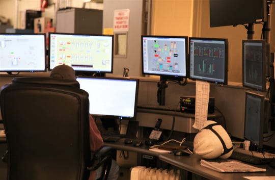 An employee watches screens inside the control room to ensure operations run smoothly at the San Juan Generating Station.