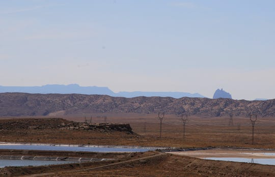 The Shiprock pinnacle can be seen, Wednesday, Sept. 25, 2019, from the San Juan Generating Station. Meanwhile, transmission lines transport electricity away from the power plant.
