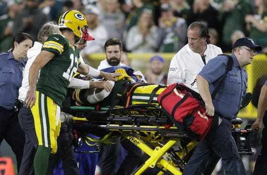 Green Bay Packers quarterback Aaron Rodgers (12) checks on Jamaal Williams (30) as he is carted off the field in the first quarter during their football game Thursday, September 26, 2019, at Lambeau Field in Green Bay, Wis.