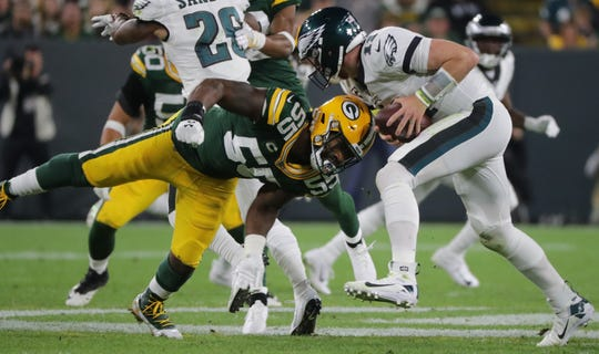 Philadelphia Eagles quarterback Carson Wentz (11) evades a sack by Green Bay Packers outside linebacker Za'Darius Smith (55) during the second  quarter of their game Thursday, September 26, 2019 at Lambeau Field in Green Bay, Wis.