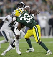 Green Bay Packers running back Aaron Jones (33) is stopped for a loss by Philadelphia Eagles defensive tackle Malik Jackson (97) in the third quarter during their football game Thursday, September 26, 2019, at Lambeau Field in Green Bay, Wis.
