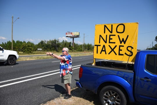 "Milton resident Jerry Couey waves and points to passing vehicles on U.S. 98 in Navarre with a ""NO NEW TAXES"" sign in the bed of his truck."