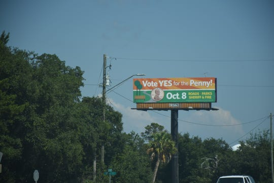 "A billboard encouraging people to ""vote YES for the penny"" is seen on Navarre Parkway on Friday."