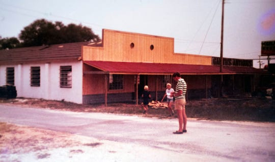 Winston Garth with his children outside his Navy Boulevard store in 1979.