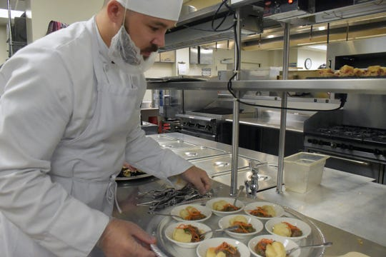 Pensacola State College culinary student Brad Stimmell prepares a tray of steak and mushroom pies with glazed carrots at an event Thursday, Sept. 26, 2019, celebrating recent donations to a culinary fund at the school in honor of Molly Martin, one of the founders of McGuire's Irish Pub.