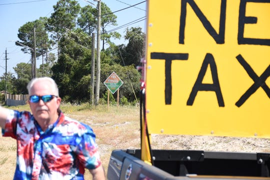 "A ""Vote YES for the Penny"" sign can be seen in the background as Milton resident Jerry Couey waves to passing vehicles with a ""NO NEW TAXES"" sign in the bed of his truck."