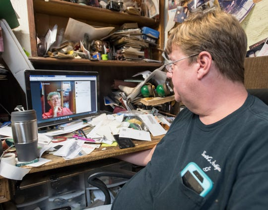 Robert Garth looks through photos of his late father, Winston Garth, at Garth's Antiques and Auction Gallery in Pensacola on Friday.