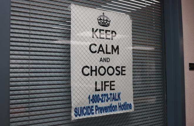 A sign with the Suicide Prevention Hotline hangs outside of a counselor's office at McClintock High School on Sept.  26, 2019.