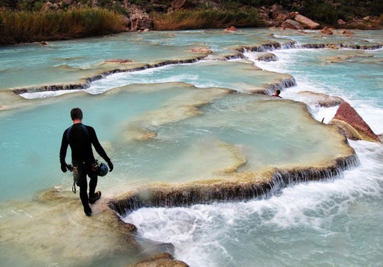 A hiker moves through the Little Colorado River on the Navajo Nation several miles upstream from the confluence with the Colorado River in Grand Canyon National Park. This part of the Little Colorado would be submerged in a 2.5 mile long reservoir from a proposed dam.