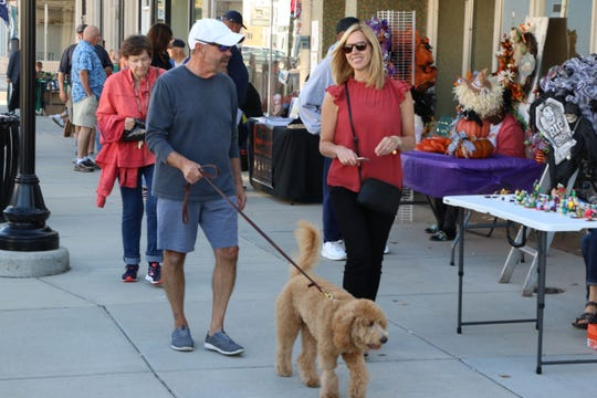 Art patrons enjoy a stroll as they take in the season's last Art Walk in Port Clinton on Thursday.