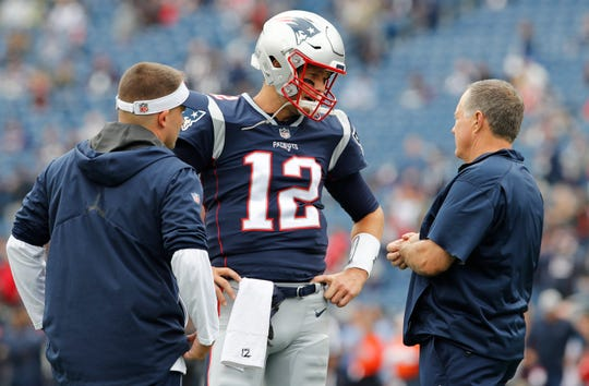 Tom Brady consults with head coach Bill Belichick and offensive coordinator Josh McDaniels.