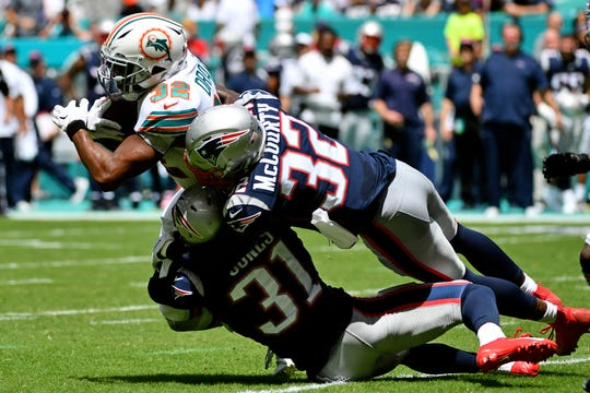 New England Patriots cornerback Jonathan Jones (31) and free safety Devin McCourty (32) bring down Miami Dolphins running back Kenyan Drake.