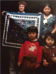 Pauline Mather holds up an example of MaiChue Her's traditional Hmong textile art in this 1980s photo. With them are two of Chue's children. This square tells the story of Chue's village and becomes the centerpiece for a quilt Mather has made for Chue.