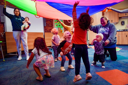 Children jump around beneath a colorful parachute during a music and movement program at the Sioux Falls downtown library on Friday, September 27.