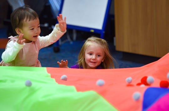 Mila Yang, left, and Elsie Suckow watch balls roll past them on a parachute at a music and movement program at the Sioux Falls downtown library on Friday, September 27.