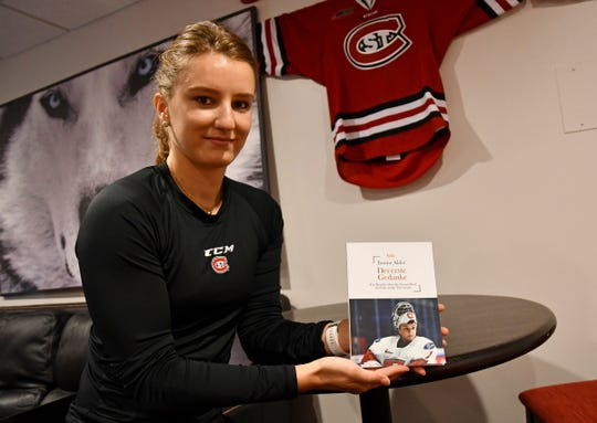 Senior goalie Janine Alder poses with her book she recently wrote Wednesday, Sept. 18, 2019, at Herb Brooks National Hockey Center.