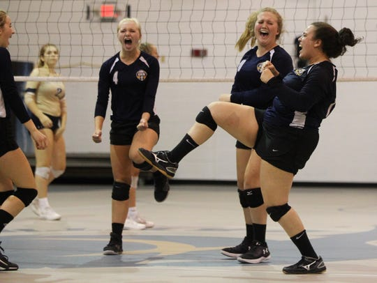 CCS seniors Sarah Banks, Kaylen Vincent and Taylor Hall celebrate a point but St. John Paul II's volleyball team rallied from down 0-2 to pull out a 3-2 home victory over Community Christian on Thursday, Sept. 26, 2019.