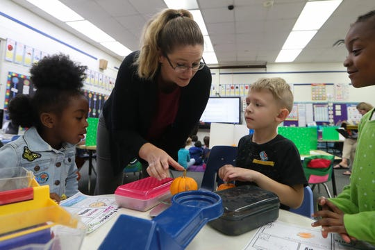 Misty Peterson, an interpreter, helps kindergarteners Bella Barber, left, Thomas Morris and Kristiana Branham with a pumpkin exploring activity at W.T. Moore Elementary School in Tallahassee, Fla. Monday, Oct. 22, 2018.