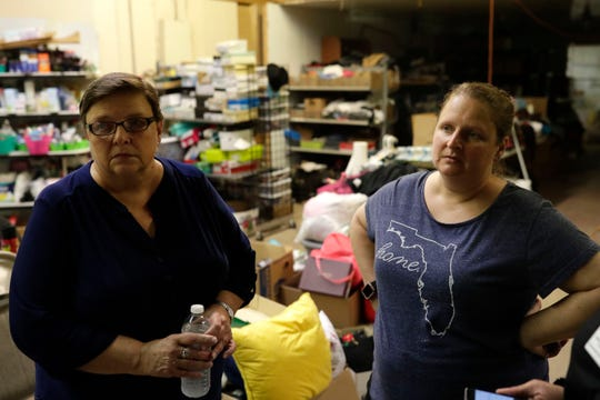 Kathy Parramore, left, and her daughter Alicia Bopp stand in the warehouse they use to store donated items that they organize and distribute to families who were severely impacted by Hurricane Michael 11 months prior.