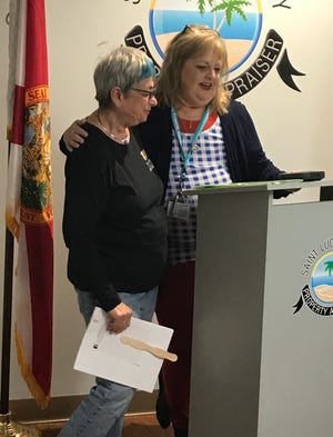 Debra Crowe, right, a St. Lucie County Appraisers Office employee and member of the Pilot Club of St. Lucie County, and Charlene Moses, president of the Pilot Club, speak at a recent staff meeting about Wreaths Across America.