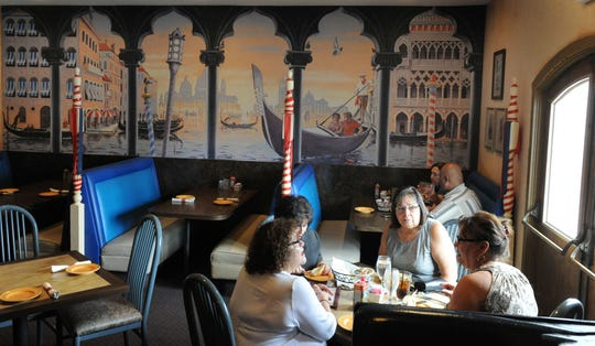 Diners chat over lunch in the Venice room at Ottavio's Italian Restaurant in Camarillo. The thematic mural painted by Stefano Falk will be preserved when the dining room is transformed into an Italian deli and market, says co-owner Julie Belvedere Thomason.