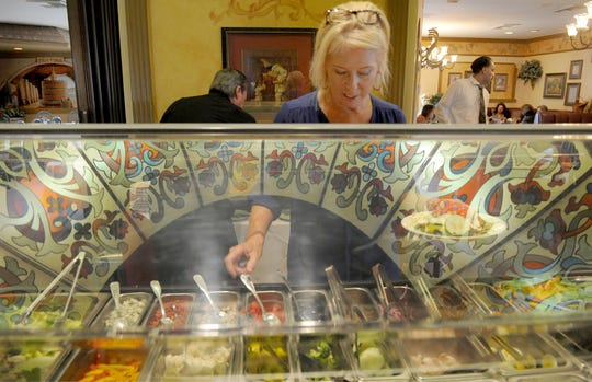 Kara Belvedere, catering director of Ottavio's Italian Restaurant in Camarillo, serves herself a salad from the all-you-can-eat lunch buffet available from 11:30 a.m. to 2 p.m. daily. The restaurant's decorative dome ceiling is reflected in the glass.