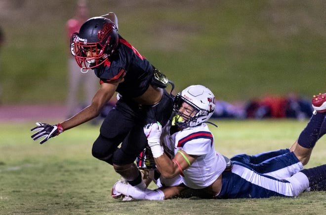 Tulare Western's Mikey Ficherin, right, takes down Hanford's Taryn Rubalcava in non-league football game on Thursday, September 26, 2019.
