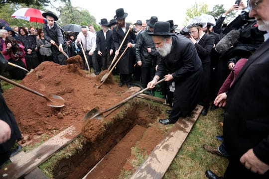 Men shovel dirt on a casket containing the ashes of victims of the Holocaust during a burial service at Congregation Sons of Israel Spring Valley Cemetery in Monsey Sept. 26, 2019. The ashes had previously been given to the Holocaust Museum and Center for Tolerance and Education in Suffern, where they had been kept for the last twenty years. Following the burial, a memorial service was held at the Holocaust Museum.