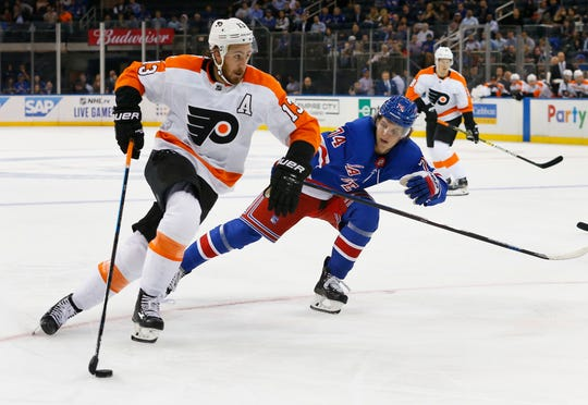 Philadelphia Flyers right wing Kevin Hayes (13) slates with the puck against New York Rangers right wing Vitali Kravtsov (74) during the first period of an NHL preseason hockey game, Thursday, Sept. 26, 2019, in New York.