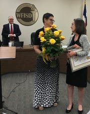 Wichita Falls High School Prinicipal Christy Nash presents WFISD Board President Elizabeth Yeager with a Yellow Rose of Texas Award Sept. 16 at a school board meeting. Nash also has a Yellow Rose of Texas Commission. Left, Place 1 Trustee Bob Payton looks on as Yeager receives the award and a bouquet.
