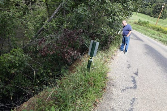 Steven Davis looks at a slip on Wilhelm Road near Chandlersville. In the past year, the road has deteriorated beyond repair. FEMA is now looking at ways to fund relocating the road to avoid future problems.
