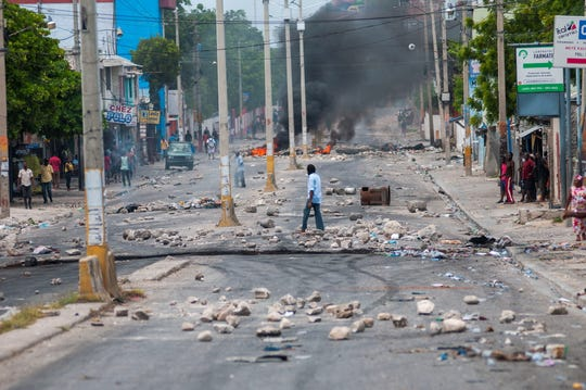 A man crosses a street full of barricades during protests in Port-au-Prince, Haiti,  Sept. 17, 2019. Port-au-Prince and several provincial capitals of Haiti lived Tuesday the second consecutive day of protests against fuel shortages, a series of demonstrations in which there has already been registered one death.