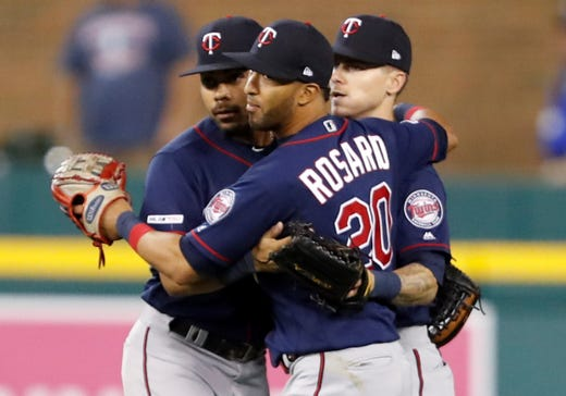 Twin center defender LaMonte Wade Jr. (30) and right defender Eddie Rosario (20) and center defender Ian Miller (41) celebrate together after their decisive victory against the Detroit Tigers.