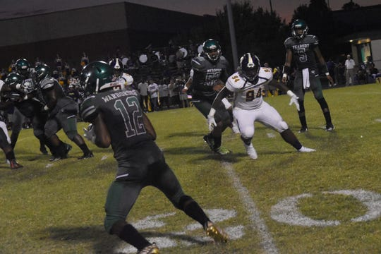 Peabody senior receiver Thomas Miles (12) catches a pass from his brother Tyriq (5), a junior quarterback, against Alexandria Senior High School Sept. 27, 2019.