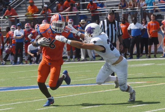 Louisiana College receiver Jarred Simpson (16) breaks a tackle against Hardin-Simmons University Cowboys Saturday, Sept. 28, 2019 in a Division III game held at Wildcat Stadium in Pineville.