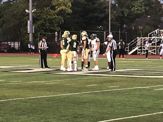 The captains for the Red Bank Catholic football team and Long Branch meet for the coin flip to start the game.