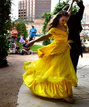 """Lauren McDonald, playing Belle, is spun by Corban Gililland as the Prince, during a scene from Disney's """"Beauty and the Beast"""" in the Adamson-Spalding Storybook Garden at the Abilene Convention Center."""