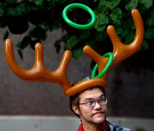 """Reuben Howe tries to position his inflatable antler rack for a child to successfully land a second ring on the tines Saturday in the Adamson-Spalding Storybook Garden at the Abilene Convention Center. The event, """"A Tale as Old as Time,"""" featured games, music and a performance from Disney's """"Beauty and the Beast"""" by theater students from Abilene Christian University."""