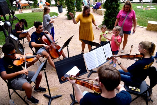 """Lillian Saunders, 5, """"conducts"""" an Abilene Youth Orchestra string quartet Saturday in the Adamson-Spalding Storybook Garden at the Abilene Convention Center."""