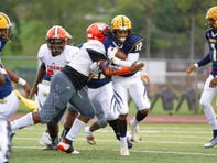BCC's O'marion Davis tries to run out of a tackle against Benton Harbor. The game was suspended at halftime and resumed on Saturday.