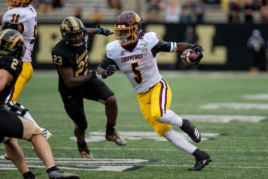 Central Michigan running back Jonathan Ward (5) rushes the ball as Western Michigan linebacker Treshaun Hayward (23) covers him during the Battle for the Cannon on Saturday, Sept. 28, 2019 at Waldo Stadium in Kalamazoo, Mich.