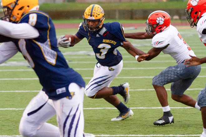 Battle Creek Central's Tyshaan Williams tries to run out of a tackle. The game was suspended at halftime and resumed on Saturday.