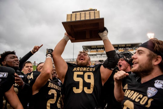Western Michigan center Luke Juriga (59) holds up the cannon trophy after they defeated Central Michigan University on Saturday, Sept. 28, 2019 at Waldo Stadium in Kalamazoo, Mich.