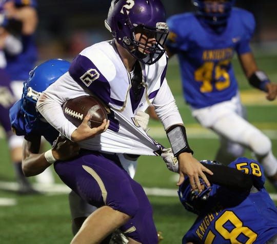 North Kitsap quarterback Colton Bower (2) is brought down by Bremerton's Luke Torres and Keith Jackmon at Bremerton Memorial Stadium on Friday, Sept. 27, 2019.